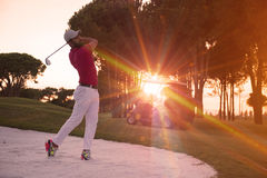 Golfer hitting a sand bunker shot on sunset Stock Photos