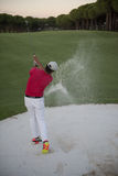 Golfer hitting a sand bunker shot on sunset Royalty Free Stock Photography
