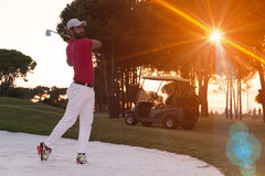 Golfer hitting a sand bunker shot on sunset Stock Images