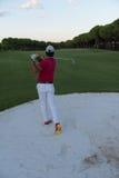 Golfer hitting a sand bunker shot on sunset Stock Photography