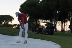 Golfer hitting a sand bunker shot on sunset Stock Photos