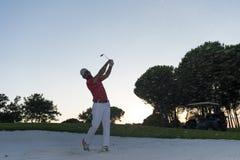 Golfer hitting a sand bunker shot on sunset Stock Images