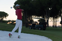 Golfer hitting a sand bunker shot on sunset Stock Image