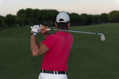 Golfer hitting a sand bunker shot on sunset. Golf player shot ball from sand bunker at course with beautiful sunset with sun flare Royalty Free Stock Photo