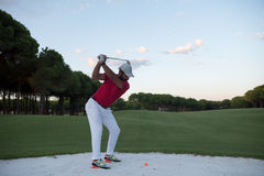 Golfer hitting a sand bunker shot on sunset. Golf player shot ball from sand bunker at course with beautiful sunset with sun flare Royalty Free Stock Photography