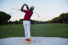 Golfer hitting a sand bunker shot on sunset Stock Photo