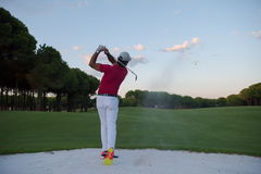 Golfer hitting a sand bunker shot on sunset Stock Image