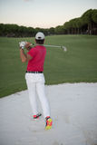 Golfer hitting a sand bunker shot on sunset Royalty Free Stock Images
