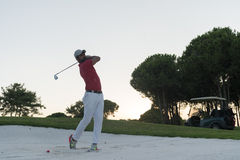 Golfer hitting a sand bunker shot on sunset. Golf player shot ball from sand bunker at course with beautiful sunset with sun flare Stock Image