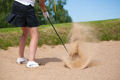 Golfer Hitting a Tee Shot in sand. A golfer strikes a tee shot on a beautiful park near lake stock photos