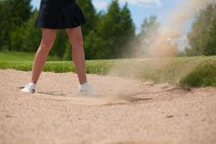 Golfer Hitting a Tee Shot in sand. A golfer strikes a tee shot on a beautiful park near lake stock photo