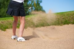 Golfer Hitting a Tee Shot in sand. A golfer strikes a tee shot on a beautiful park near lake royalty free stock photography