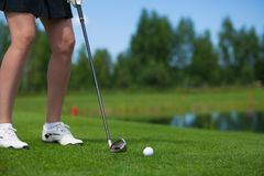 Golfer Hitting a Tee Shot. A golfer strikes a tee shot on a beautiful park near lake royalty free stock photography