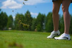 Golfer Hitting a Tee Shot. A golfer strikes a tee shot on a beautiful park near lake royalty free stock images