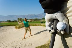 Golfer Holding Ball With Man Playing In Background royalty free stock photography