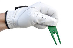 Golfer Holding a Ball Mark Repair Tool. Golfer Holding a Green Ball Mark Repair Tool (or Pitchfork Royalty Free Stock Photos
