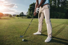 Golfer holding club and hitting ball on green grass. Cropped shot of golfer holding club and hitting ball on green grass Royalty Free Stock Images