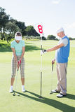 Golfer holding eighteenth hole flag for partner putting ball Royalty Free Stock Images