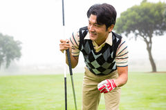 Golfer holding golf ball and club Stock Image