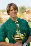 Golfer Holding Golf Trophy. Portrait of a happy young male golfer holding a shiny golf trophy Royalty Free Stock Photo