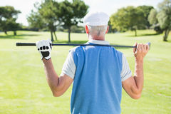 Golfer holding his club behind his head. On a sunny day at the golf course Royalty Free Stock Image