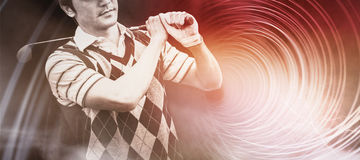 Composite image of golfer holding his club on shoulder. Golfer holding his club on shoulder against futuristic shiny spiral on black background Stock Images