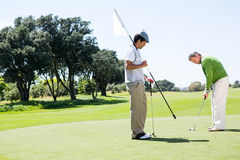 Golfer holding hole flag for friend putting ball Stock Photography