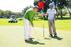 Golfer holding hole flag for friend putting ball Stock Images