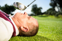 Golfer holding tee in his teeth. On a sunny day at the golf course stock images