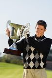 Golfer holding trophy Royalty Free Stock Images