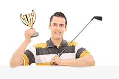 Golfer holding a trophy behind a blank panel Stock Photography