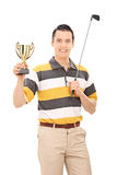 Golfer holding a trophy and golf club. Golfer holding a trophy and a golf club isolated on white background Royalty Free Stock Photos