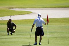 Golfer at hole Royalty Free Stock Image