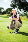 Golfer kneeling holding his golf club Stock Photo