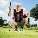 Golfer kneeling watching gold ball Royalty Free Stock Photo
