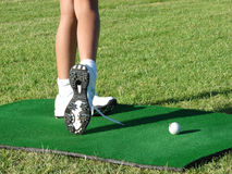 Golfer Legs. Legs of a young female golfer after a practise swing during a golf lesson on a range mat Stock Image