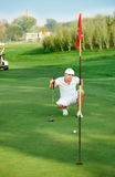 Golfer lining up a putt. Young golfer lining up a putt Stock Photos