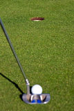Golfer lining up a short putt - focus on the hole. View from behind a putt on a golf green, as the golfer lines up a short putt. Short depth of field with focus Royalty Free Stock Images