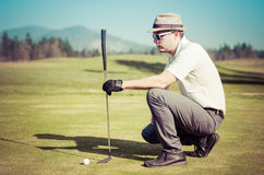 Golfer looking golf shot with club. On course putting on green while on vacation. Golfer is chipping a golf ball onto the green with driver golf club Stock Photo