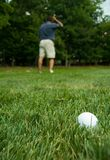 Golfer looking for his ball. Camera zooming on golf ball with puzzled golfer in the back Royalty Free Stock Photo