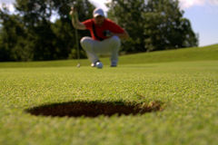 Golfer looking at hole. Golfer crouching on green with ball looking at hole in foreground Stock Image