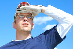 Golfer Looks to the Sky. A golfer shades his eyes as he follows the ball soaring towards the flag Stock Photography