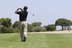 Golfer making fairway shot. Male golfer off fairway to green with iron shot stock photography