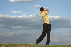 Golfer - Man. Man swinging a golf club late after noon Stock Photos