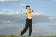 Golfer - Man. Man swinging a golf club late after noon Stock Photo