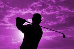 Golfer - Man. Man swinging a golf club late after noon Stock Images