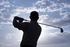 Golfer - Man. Man swinging a golf club late after noon Royalty Free Stock Photography