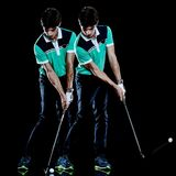 Golfer man golfing golf swing isolated black background multiple exposure. One caucasian young golfer man golfing golf swing isolated on black background with stock photo