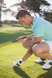 Golfer man placing golf ball on tee. While crouching at field Royalty Free Stock Photos