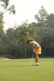 Golfer. Mature Asian woman playing golf Royalty Free Stock Image
